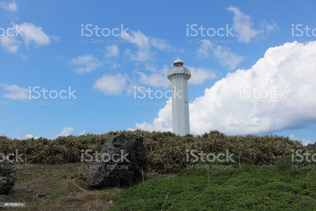 A white lighthouse on the upper hill. Blue sky and sea, The beach and coastline beside the ocean in Miyako island, Okinawa, Japan stock photo