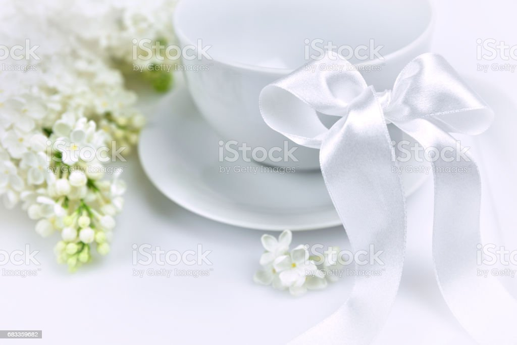 White lilac with white cup and a ribbon stock photo