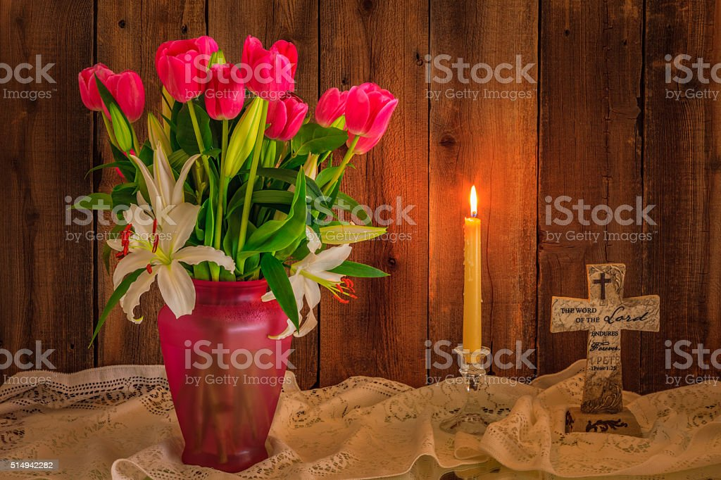 White Lilies, pink tulips ,cross, candle against rustic wood (P) stock photo