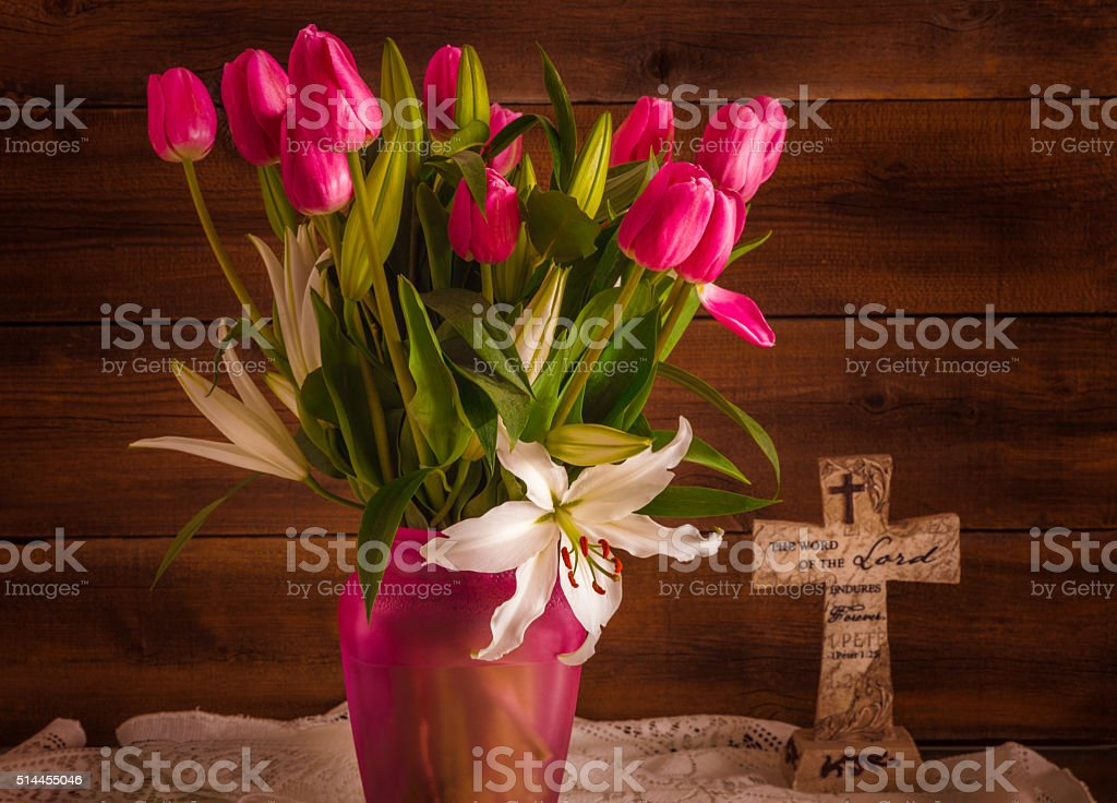 White Lilies, pink tulips with cross against rustic wood (P) stock photo