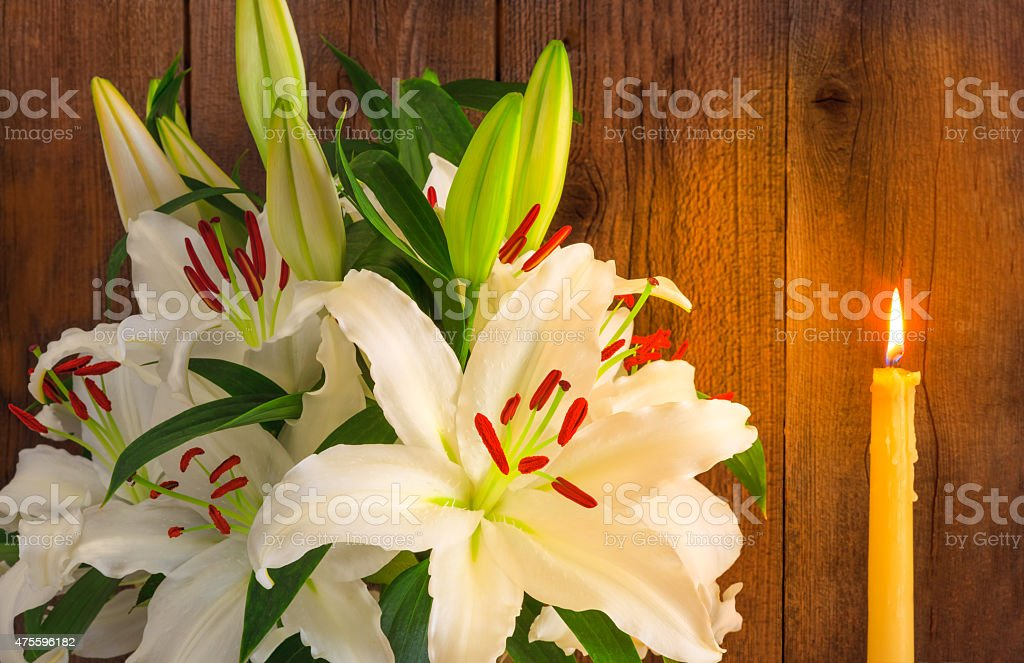 White lily bouquet with a lit candle against  wood (P) stock photo