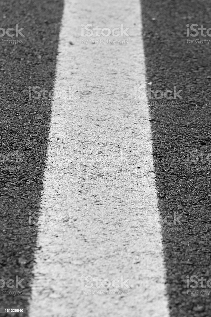 white line painted across the black asphalt road royalty-free stock photo