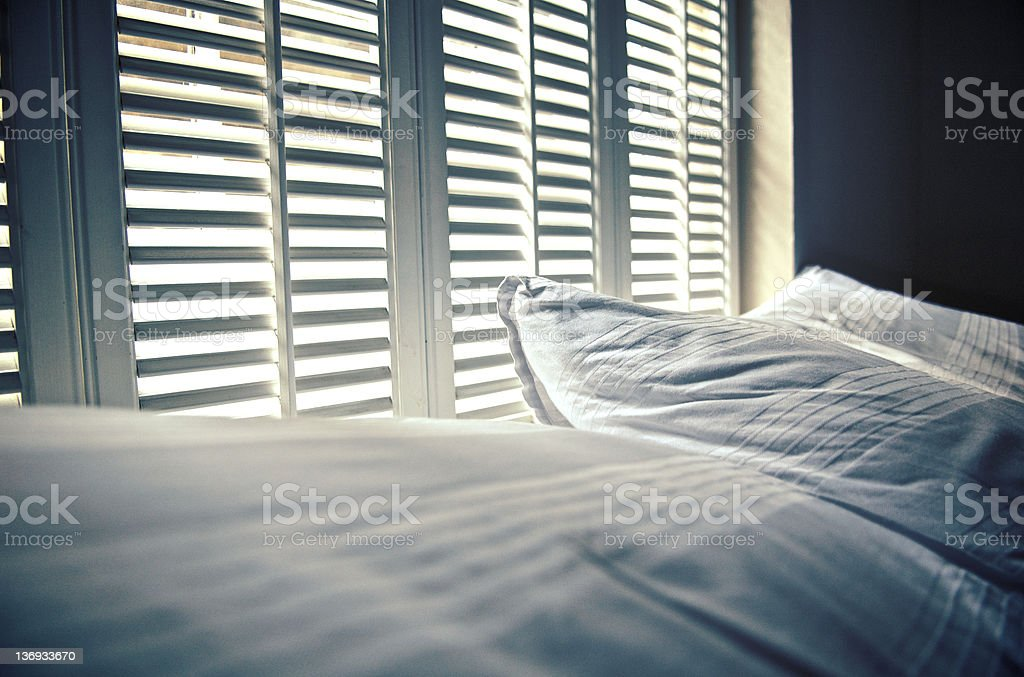 White linen against white shutters with white light behind stock photo