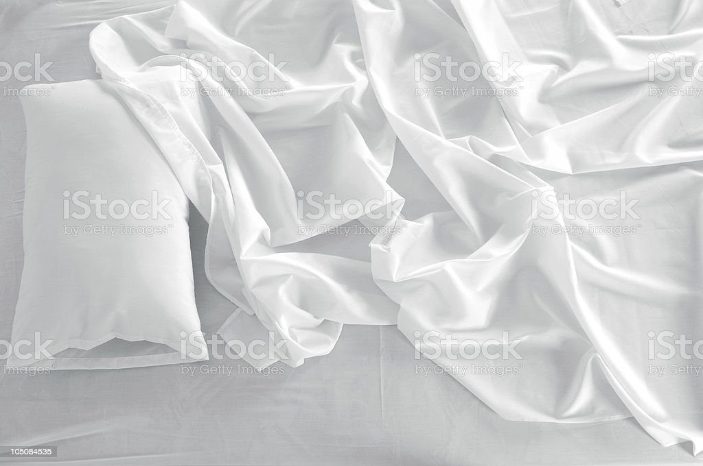 A white linen messed up bed sheets and a white pillow stock photo