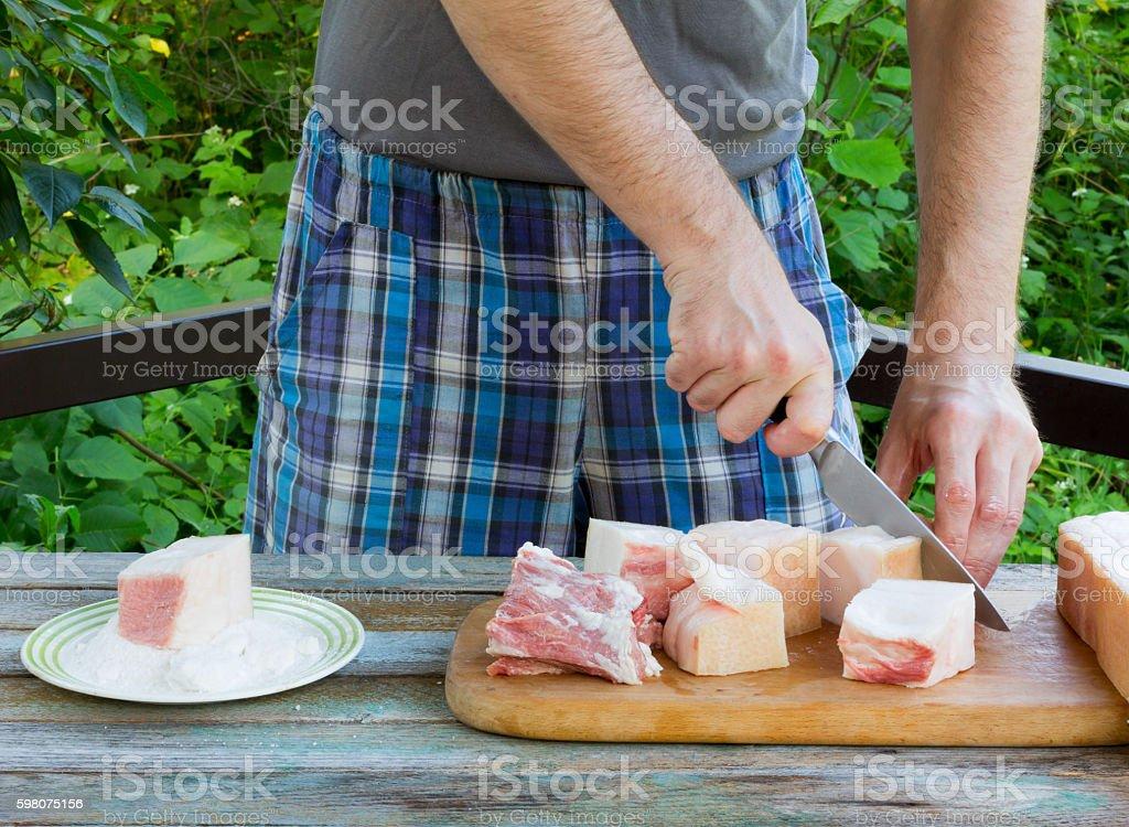 white man cuts lard on salting stock photo
