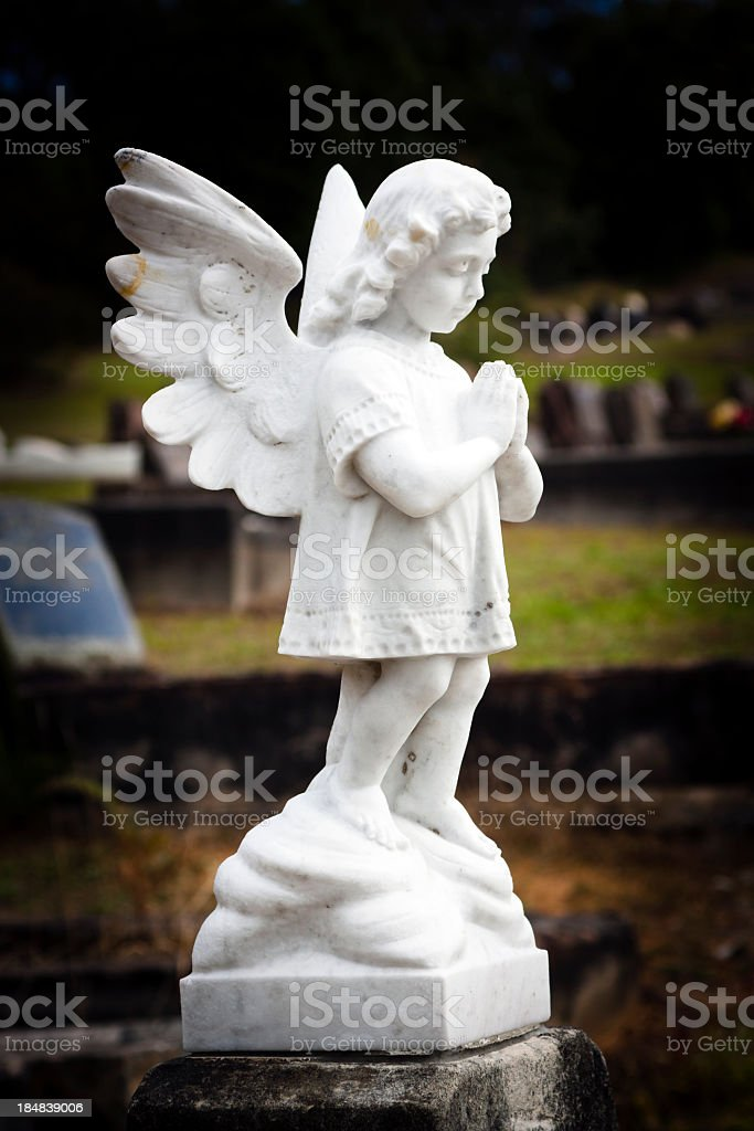 White marble statue of praying little angel in cemetery, vignette stock photo