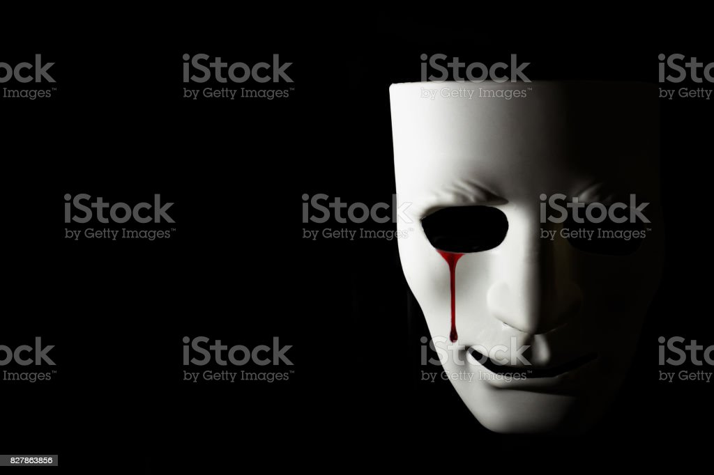White mask and bloody tear on black background stock photo