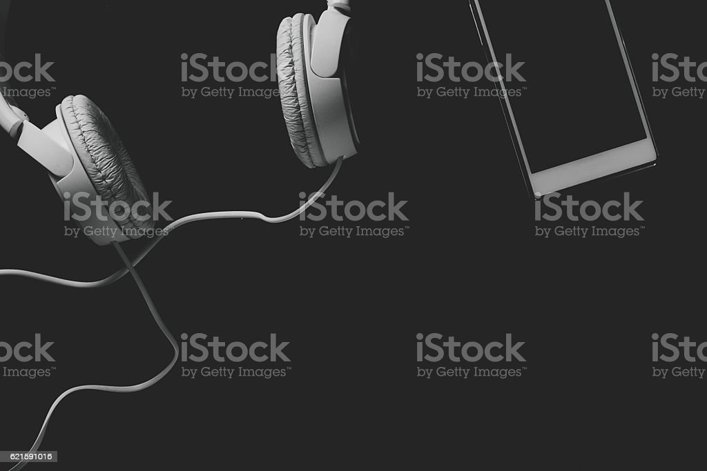 White mobile phone and headphones on a black background stock photo