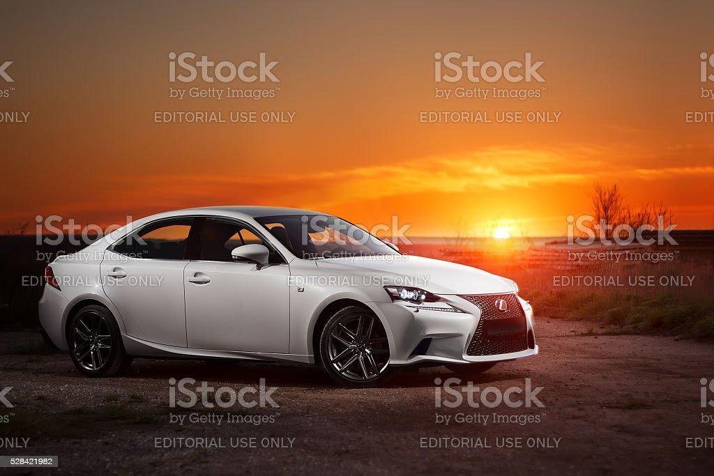 White modern car Lexus stay on road at beautiful sunset stock photo