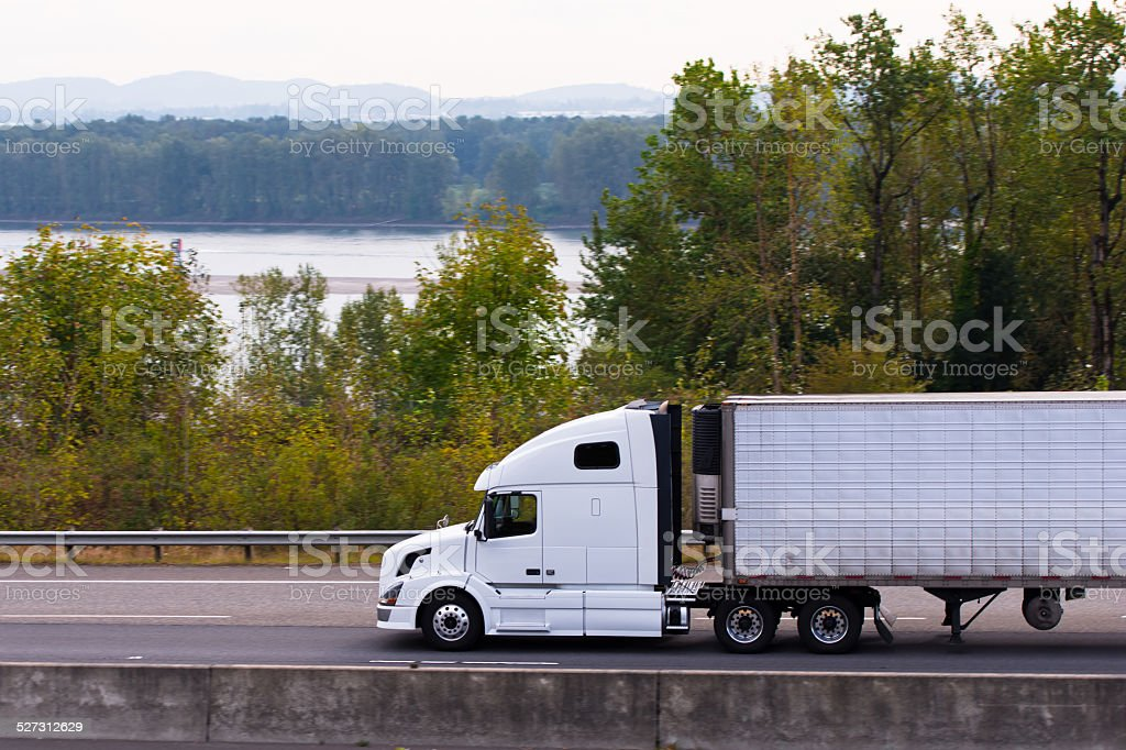 White modern semi truck reefer on highway along river Columbia stock photo