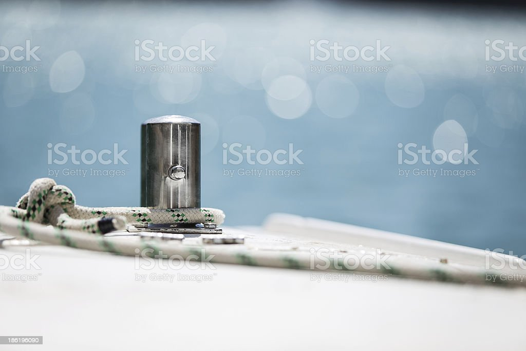 White mooring rope tied around steel anchor on boat royalty-free stock photo