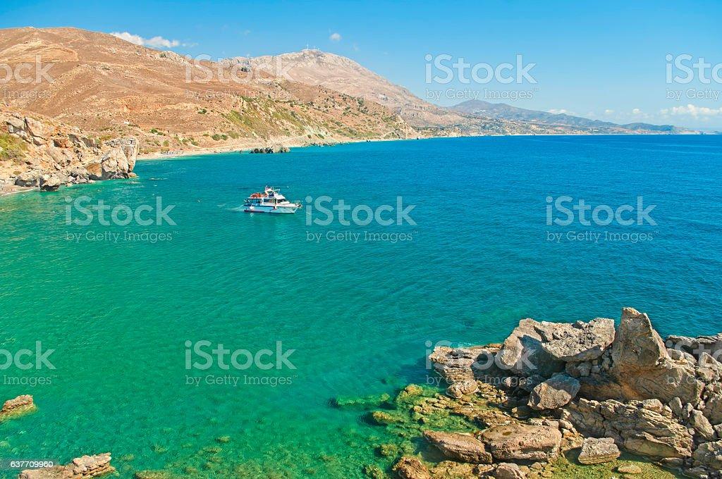 white motor boat at  rocky coast stock photo