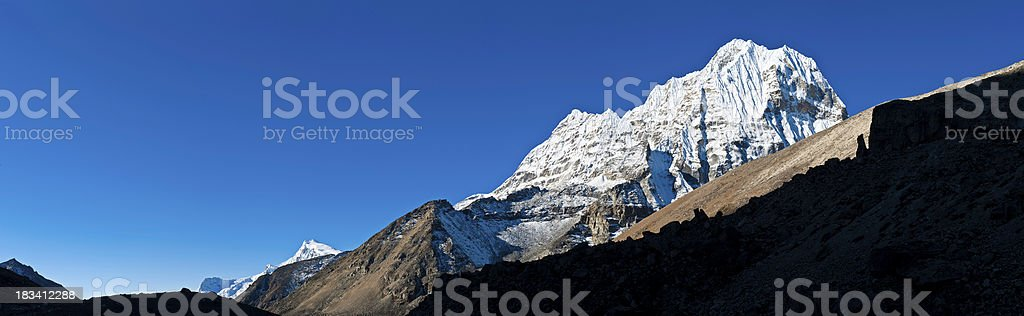 White mountain blue sky black rocks panorama Kangtega Himalayas Nepal stock photo