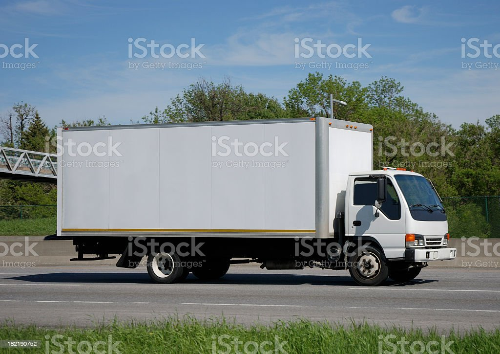 White moving truck driving on the road royalty-free stock photo