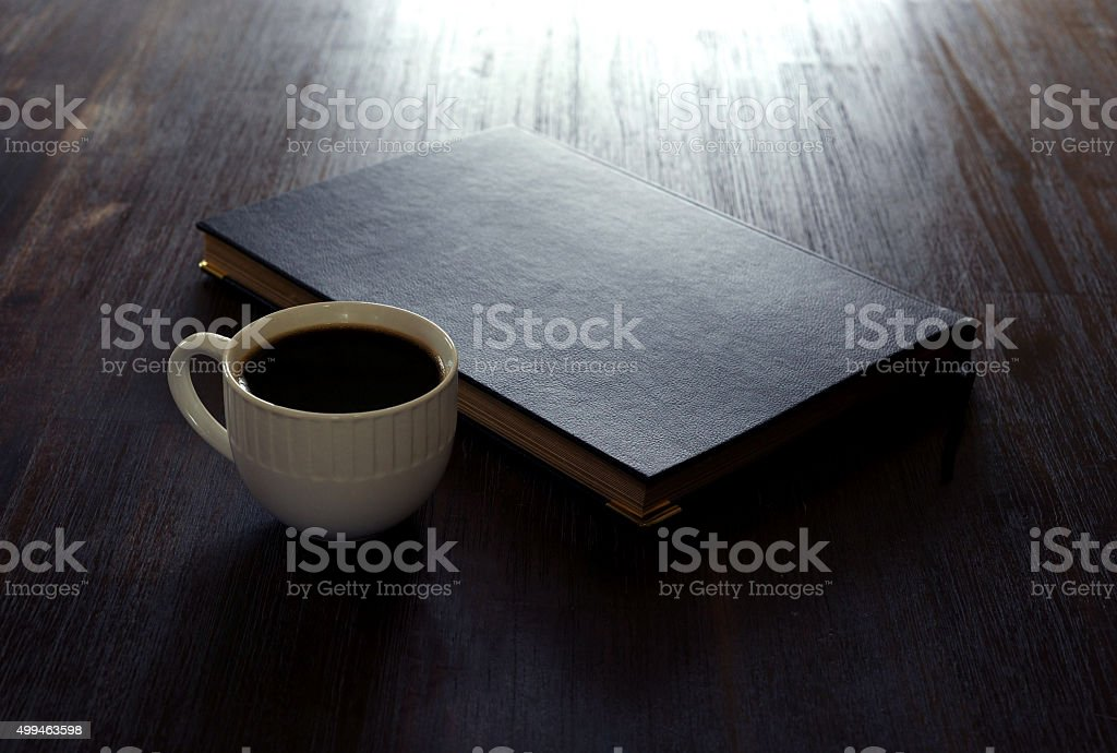 White mug of coffee and black book on table stock photo