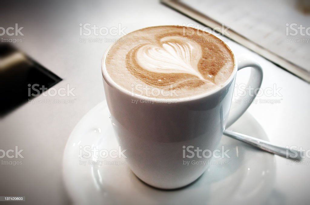 White mug of coffee with heart design in foam royalty-free stock photo