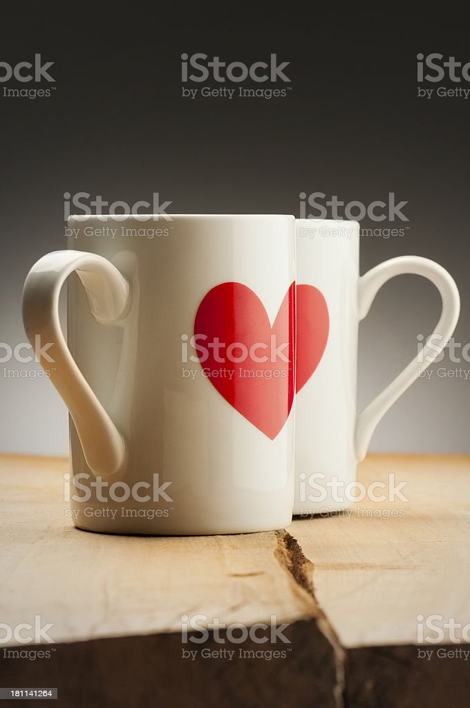 White mugs with red hearts on wooden table royalty-free stock photo