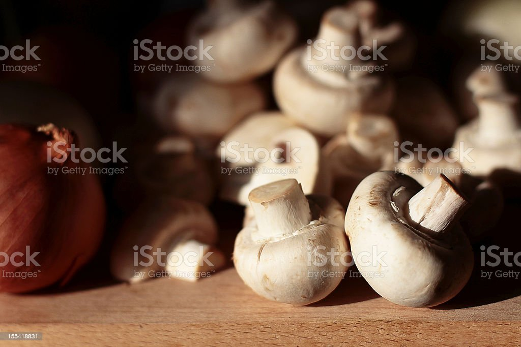 White mushrooms on a wooden chopping board royalty-free stock photo