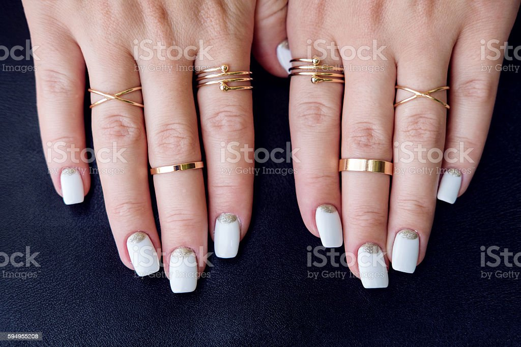 White nail art manicure, hands with fashion gold rings stock photo