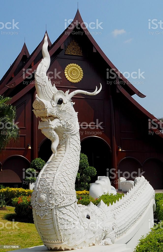 White Naka statue in front of wooden Thai church stock photo