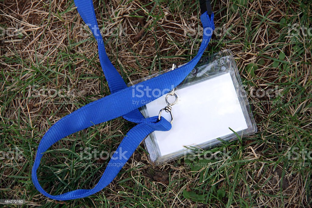 White name tag, blue lanyard, in the grass.  Copy space. stock photo