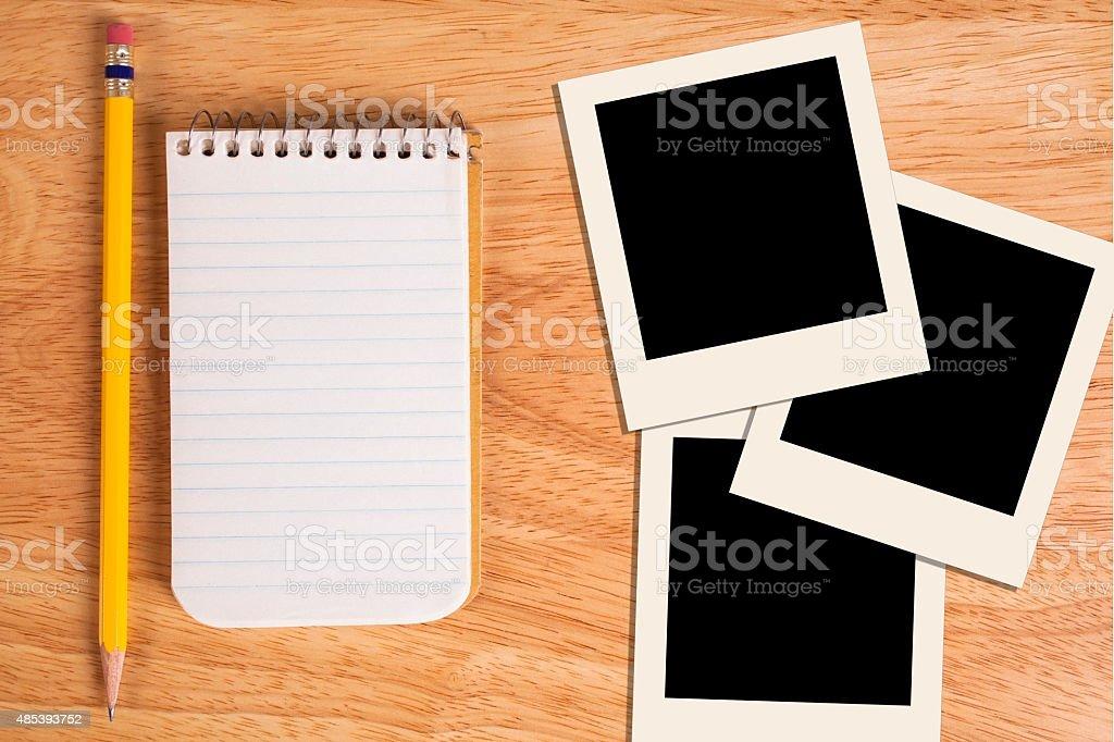 White notepad, pencil with polaroid-style photos on desk. stock photo