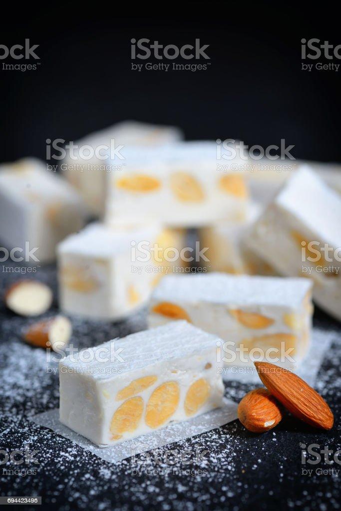 White nougat with almonds on black ardesia plate stock photo
