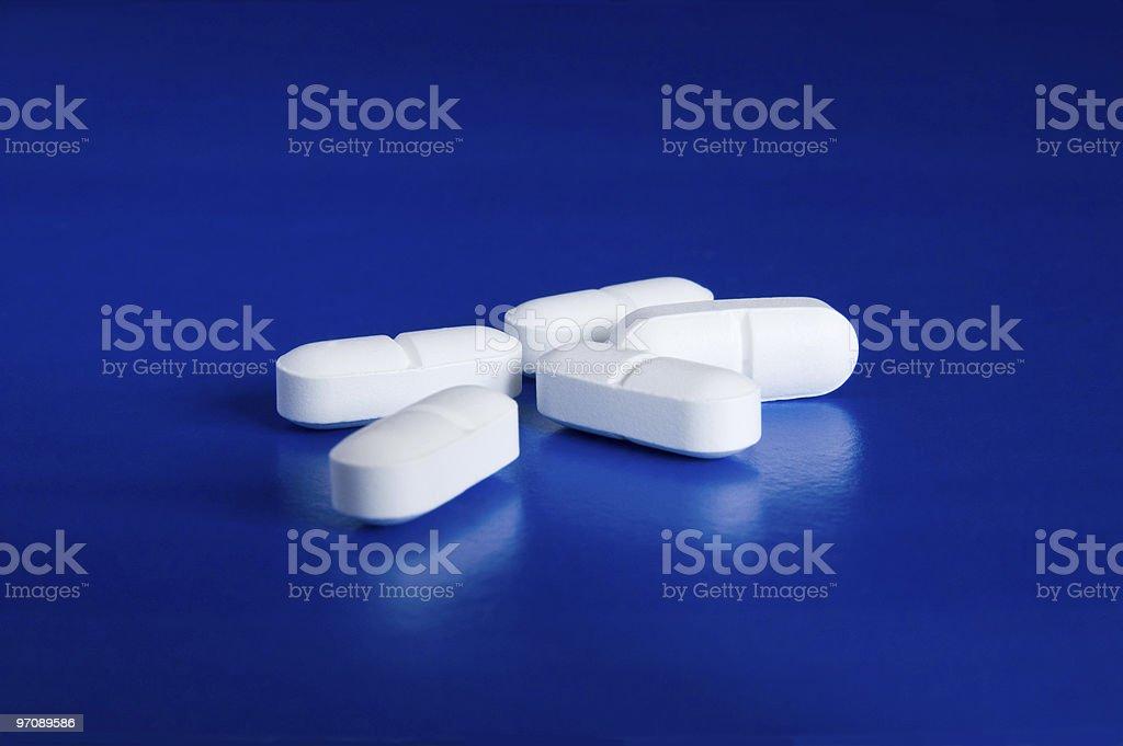 White oblong pills against blue background stock photo