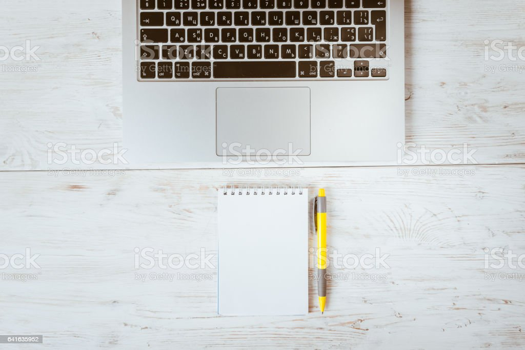 White office desk table with laptop, pen, and notebook. stock photo