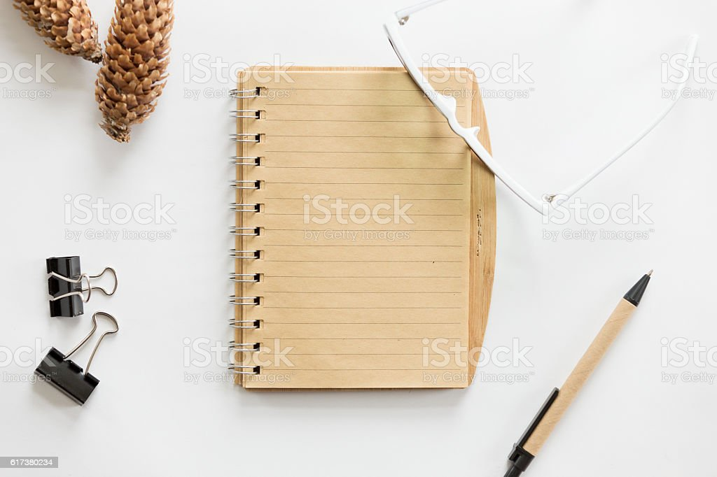 White office desk with glasses, pen, notebook and cone on stock photo