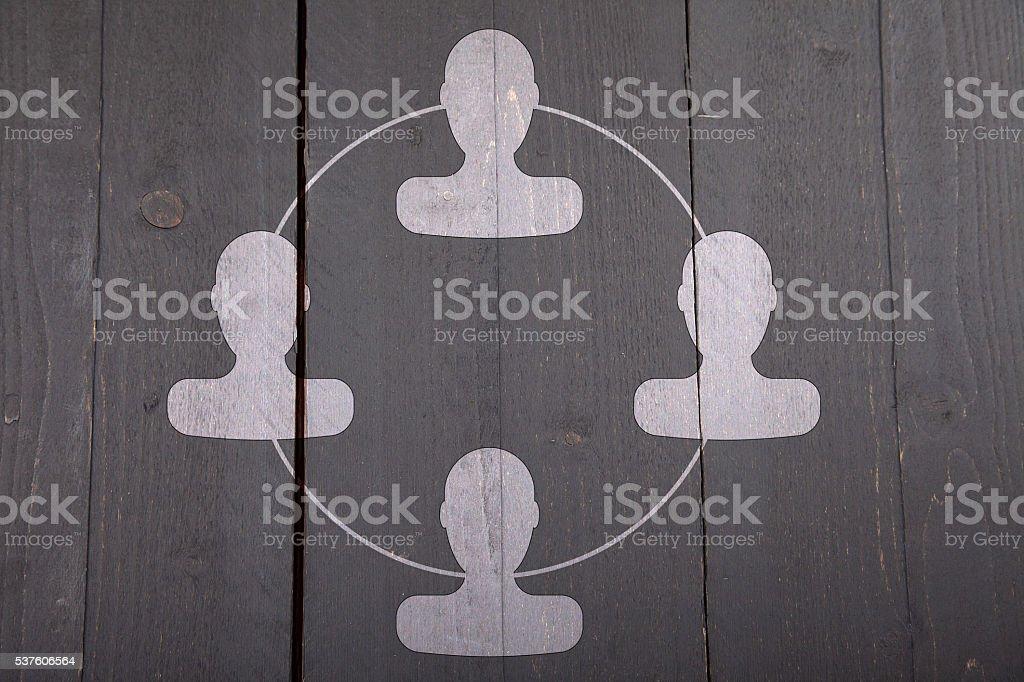 White organigram with white heads on dark black wooden background stock photo
