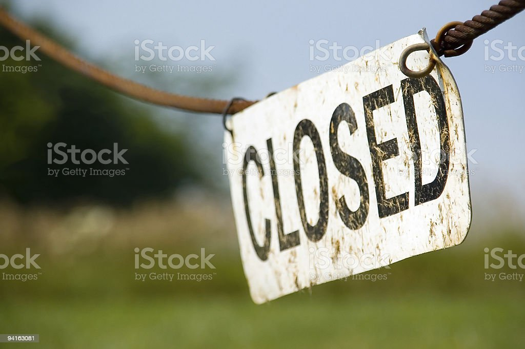 White Outdoor Metal Closed Sign Hanging on a Cable royalty-free stock photo