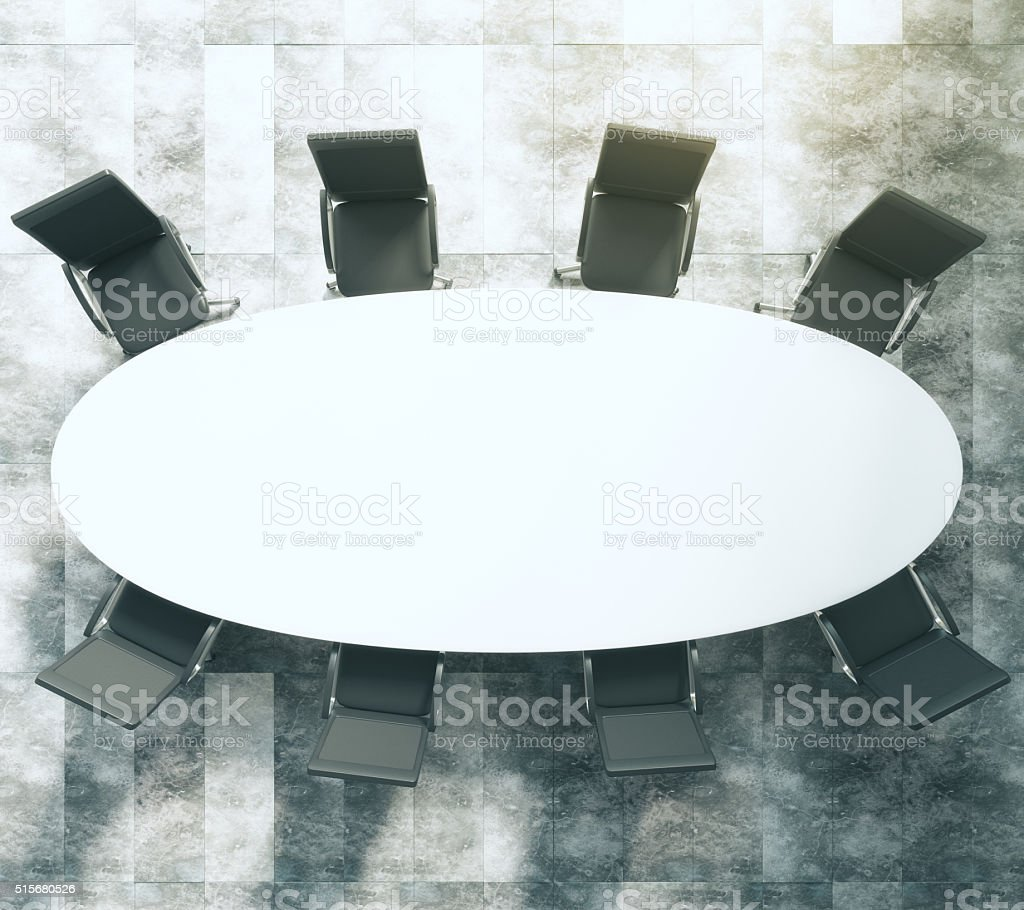 White oval conference table with black leather chairs on concret stock photo
