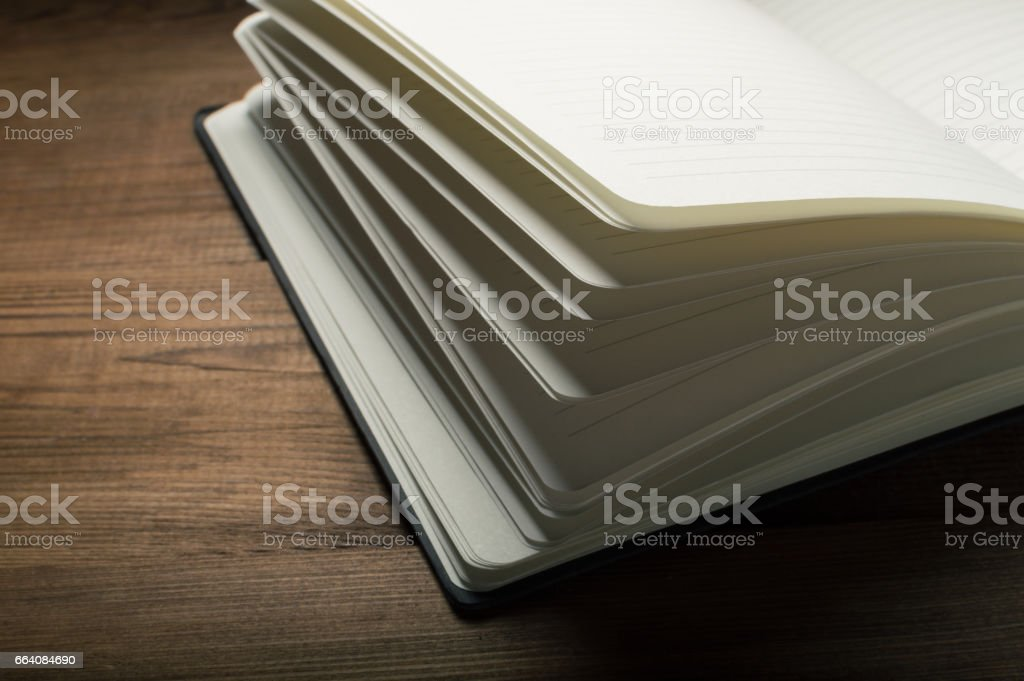 White pages of notepad on the wooden table stock photo
