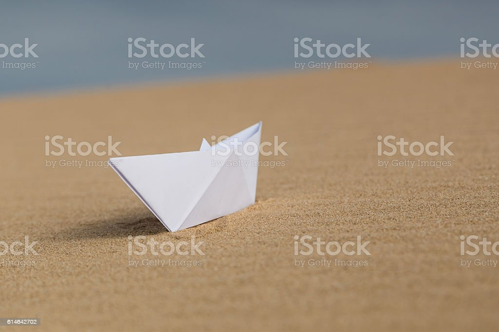 White paper boat on the beach stock photo
