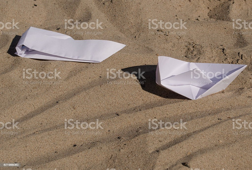 white paper boats on sand