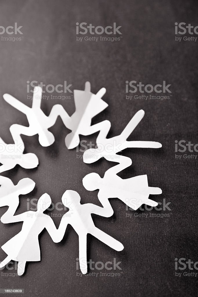 White paper chain of people in a circle on black background stock photo