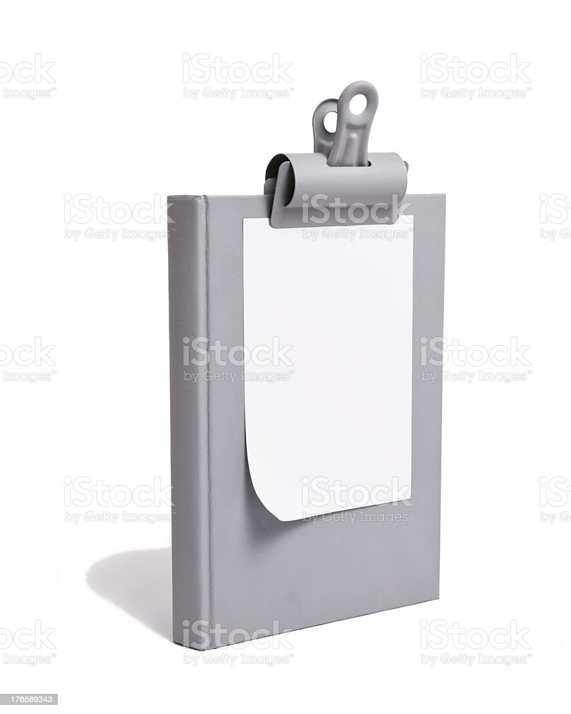 White Paper Clipped to Grey Book royalty-free stock photo
