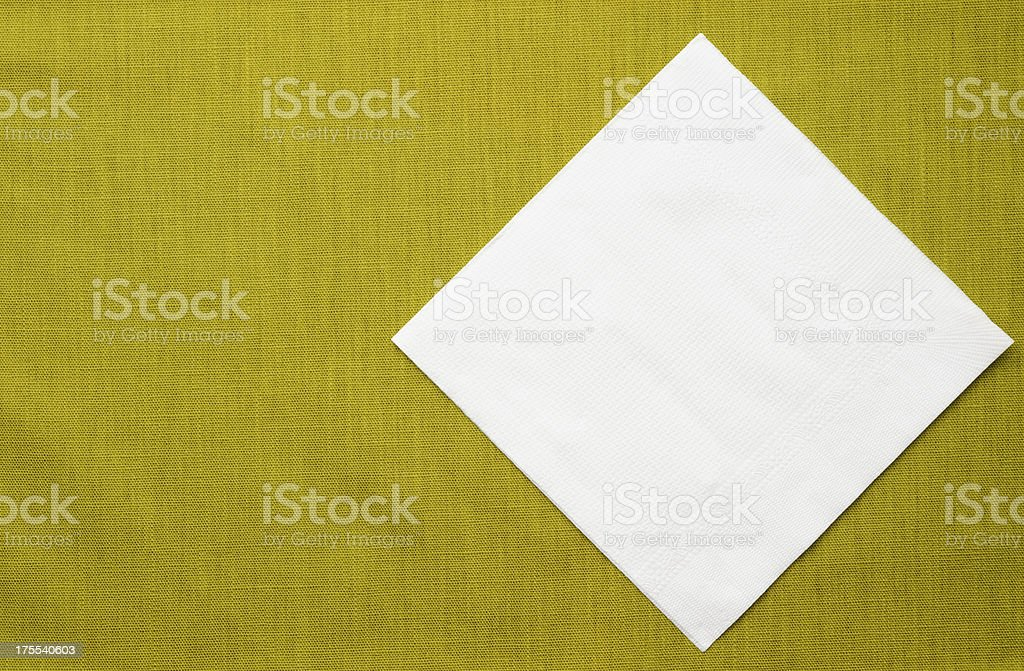 White paper napkin on green tablecloth with copy space stock photo