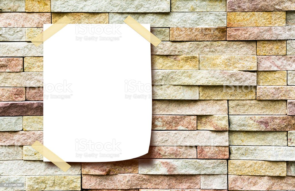 white paper note on the brick wall stock photo