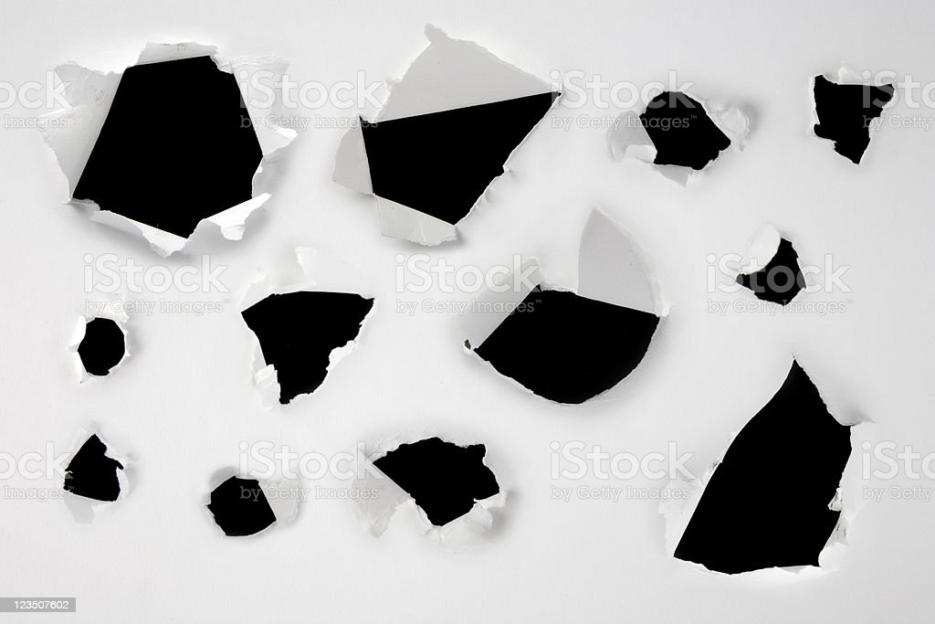 White paper over a black background with holes ripped in it stock photo