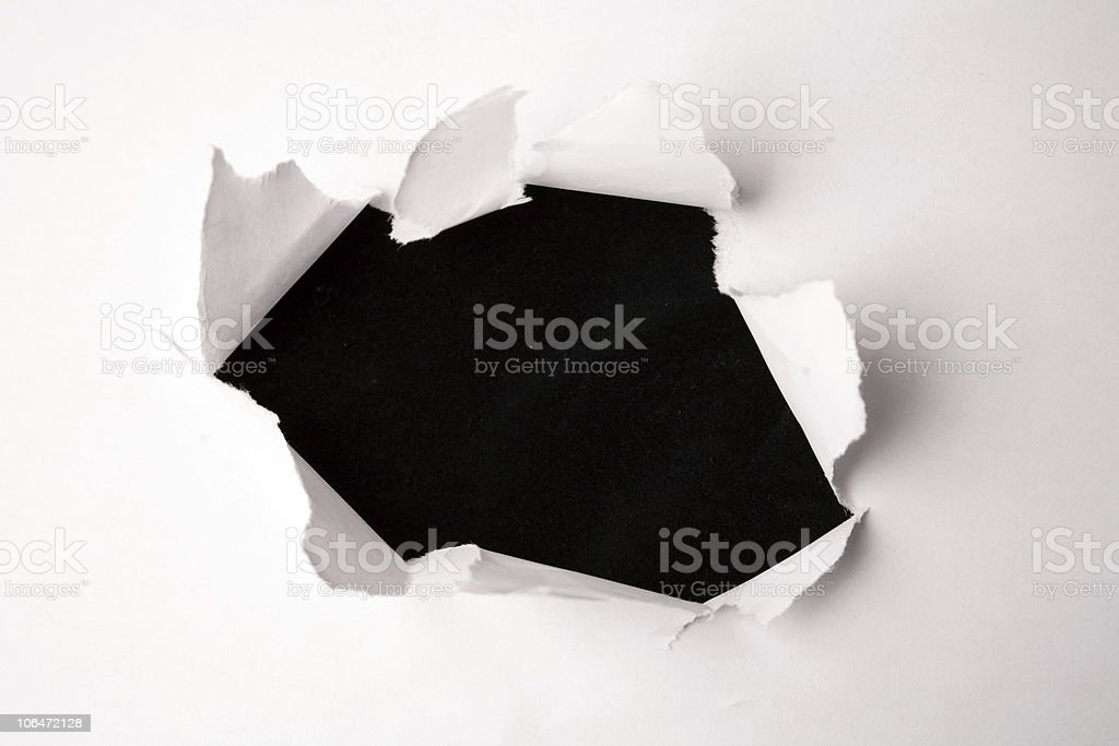 White paper sheet with fist like tear in the middle stock photo