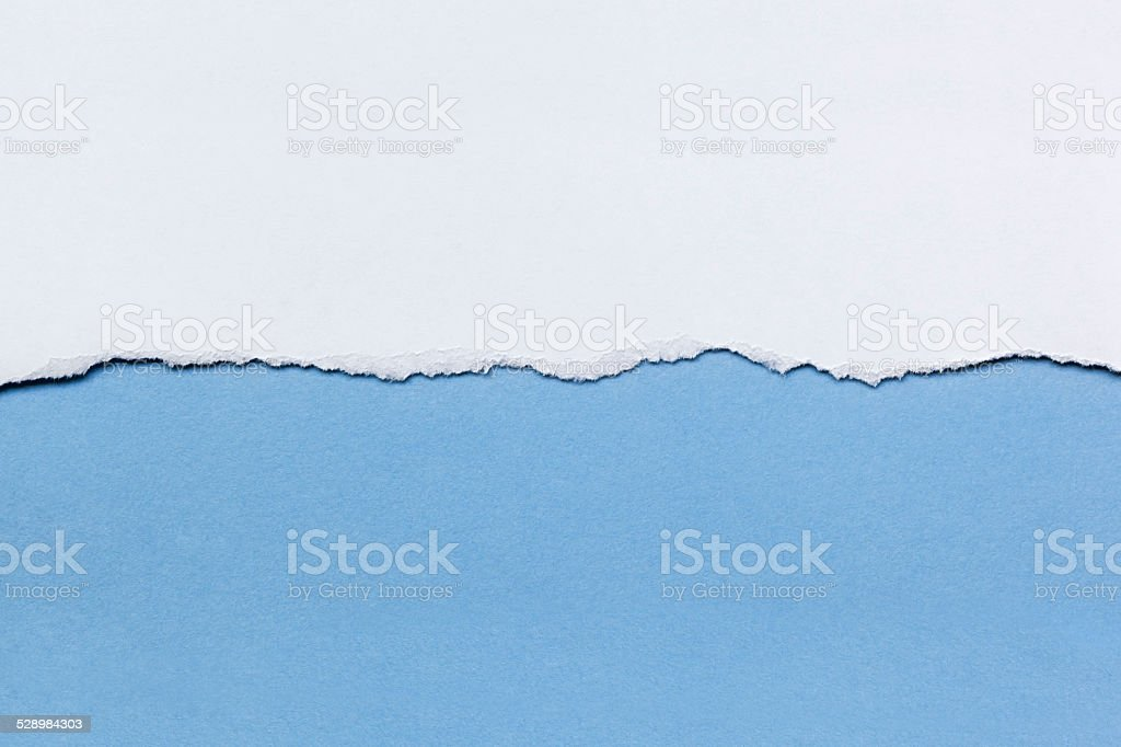 White Paper Tear over Blue stock photo