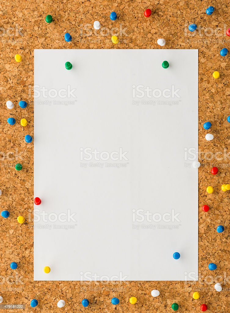 white paper with blue push pin on cork board stock photo