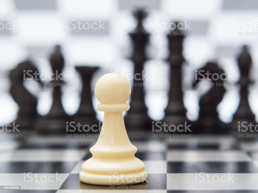White pawn against the background of dark chess pieces stock photo