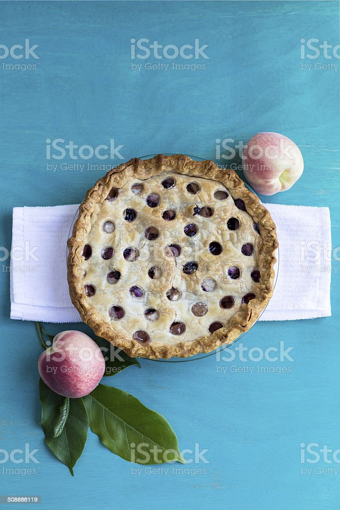 White peach and blueberry pie on a blue table stock photo