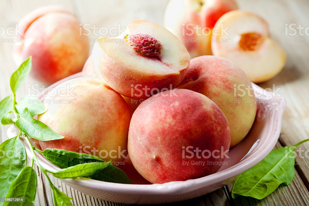 White peaches in a bowl with green leaves stock photo