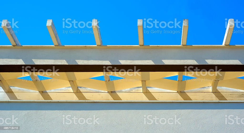 White pergola roof beans and blue sky mesh pattern stock photo
