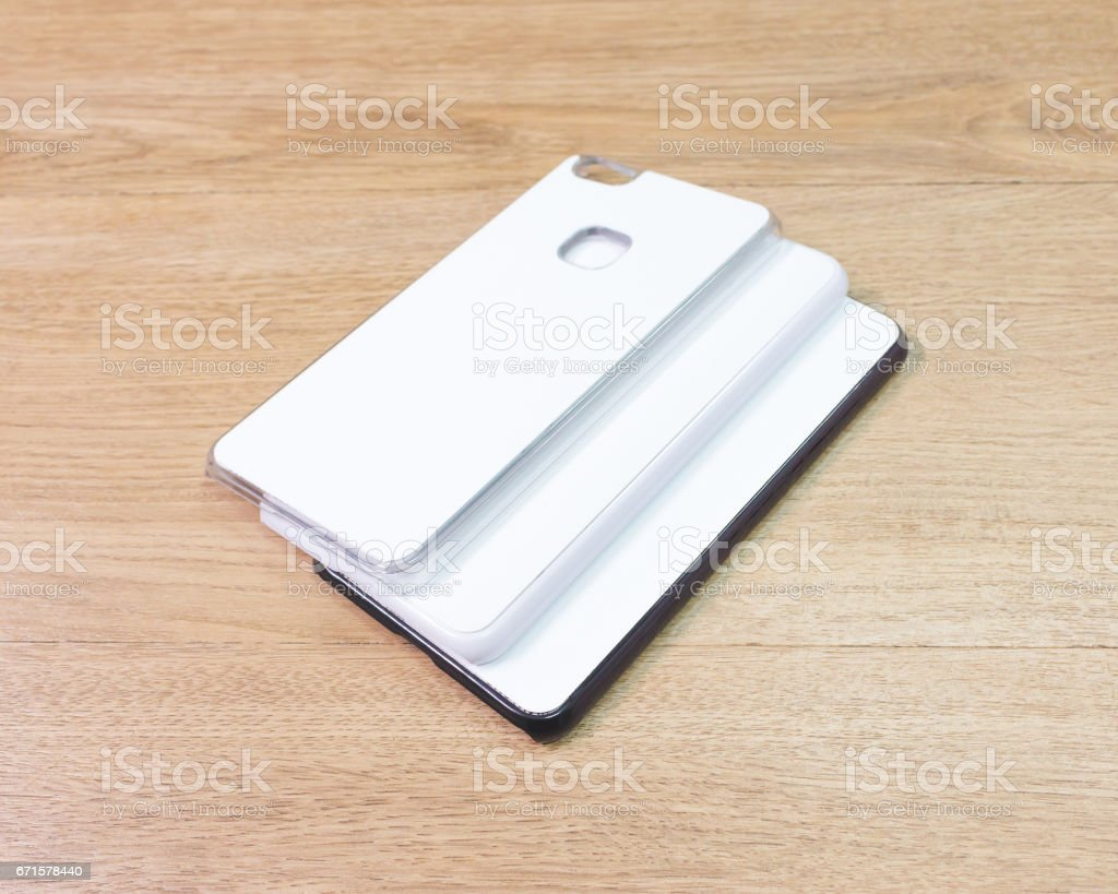 White phone cases on wooden background. stock photo
