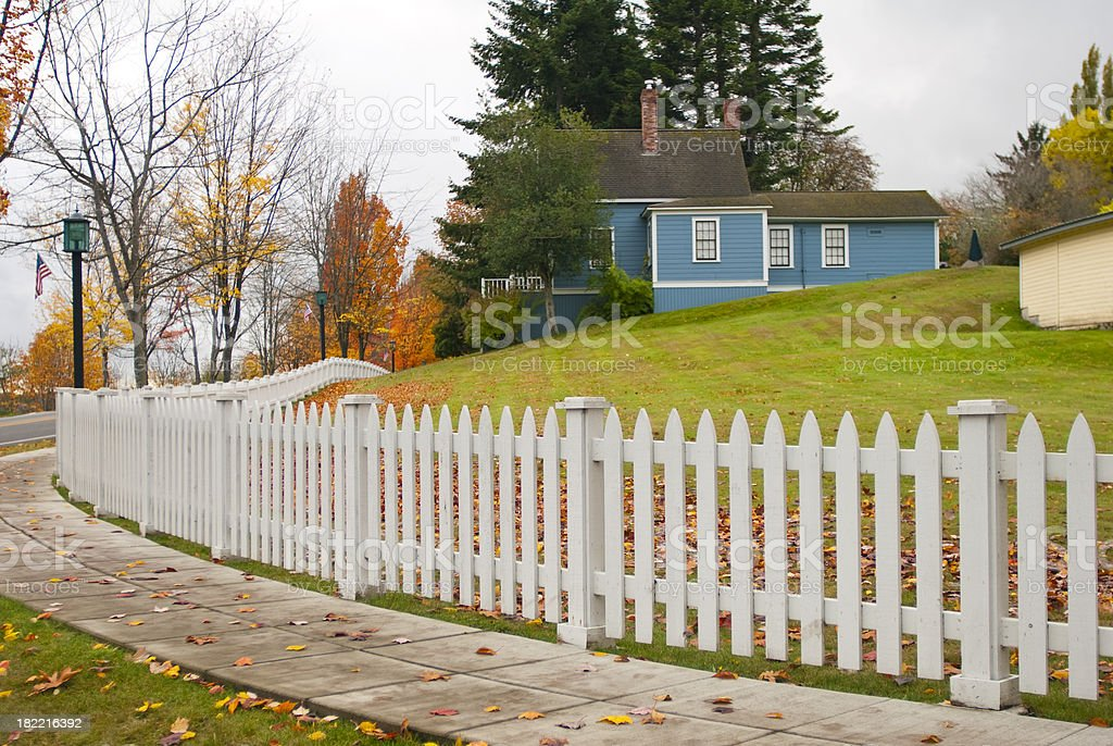 White picket fence and big green lawn next to house royalty-free stock photo